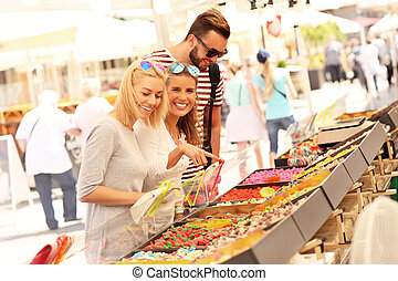 Group of friends buying jelly sweets on market - A picture...