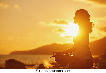 Pregnant woman practicing yoga in lotus position on beach at sunset