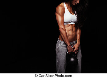 Female doing body building exercise with kettle bell -...