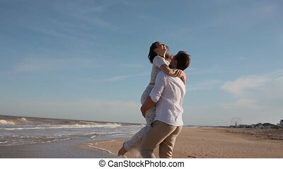 Young man take his woman on his hands and circlingView on...