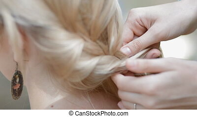 Weaving braids - Hairdresser makes hair braiding on blond...