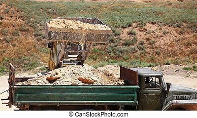 Excavator loading heavy duty dumper truck with rocks