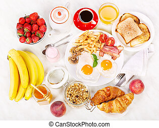 Breakfast  with fried eggs, coffee, orange juice, toasts and fruits