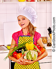 Child cooking at kitchen - Teenager girl holding vegetable...