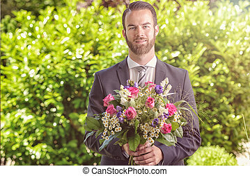 Handsome man in a suit carrying flowers - Handsome bearded...