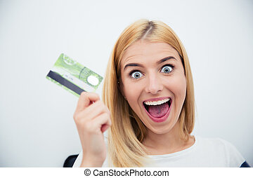Cheerful young woman holding bank card over gray background