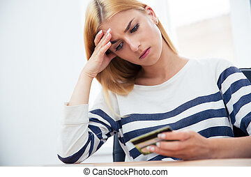 Woman holding bank card - Unhappy casual woman holding bank...
