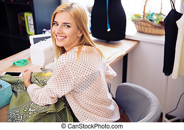 Smiling woman using a sewing machine