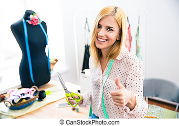 Female tailor showing thumb up - Smiling female tailor...