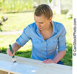 mujer, con, cepillo, Pintura, de madera, furniture.,