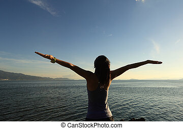 young cheering woman jogger open arms at sunrise...