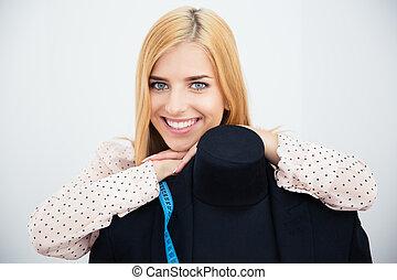 Female designer leaning on the mannequin