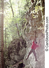 climber in back light - climbing man on a rock wall at back...