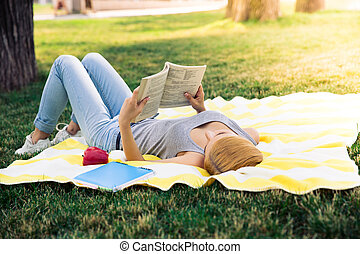 Young girl reading book outdoors - Young girl lying in park...