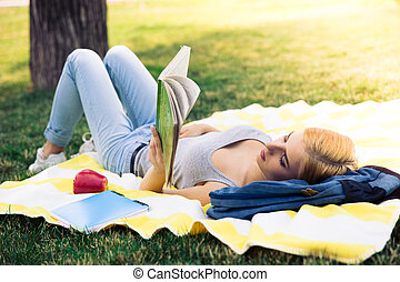 Young girl reading book outdoors - Young girl lying and...
