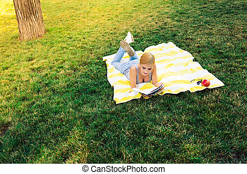 Woman lying on mat and reading book - Beautiful young woman...