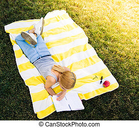 Woman lying on mat and reading book - Top view portrait of a...