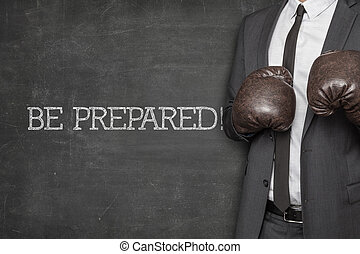 Be prepared on blackboard with businessman wearing boxing...