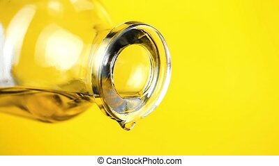 pouring olive oil with the bottle on yellow background,...