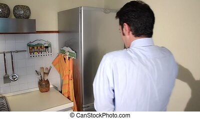 man looking in his empty fridge
