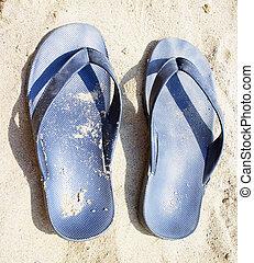 Flip flop - Black flip flop over sand beach, vertical image