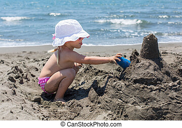young lady is building a sand castle on the sea shore