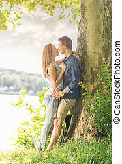 Couple in love on the lake, beneath the trees, kissing