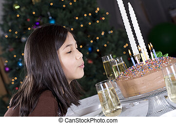 Little girl blowing out her birthday cake candles