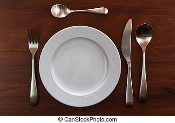 empty plate - empty white plate with cutlery over wooden...