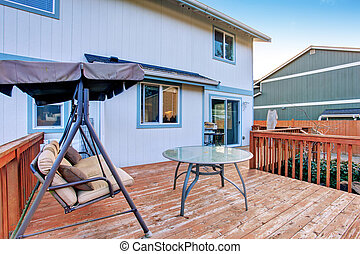 large wooden deck with swinging bench, and glass table.