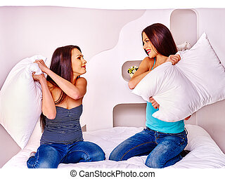 Lesbian women at pillow fights in bed.
