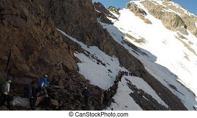 Long line of tourists in the Mountains - Long line of...