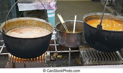 Outdoor Cauldrons with Food - The traditional meat soup is...