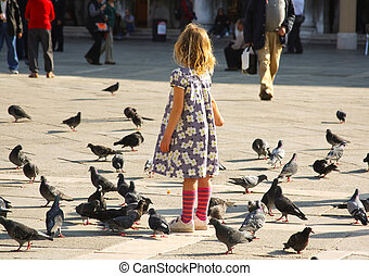 girl and pigeons - a little girl feeding a flock of pigeons