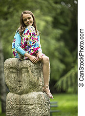 girl sitting on a stone totem