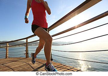 young fitness woman legs running on seaside wooden boardwalk