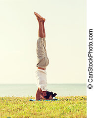 man making yoga exercises outdoors - fitness, sport, people...