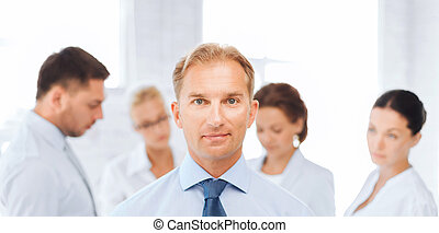 businessman in office with group on the back - business,...