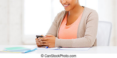 african woman with smartphone in office