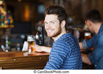 happy young man drinking beer at bar or pub