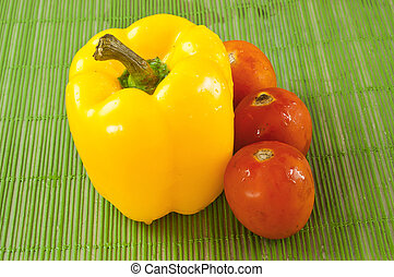 Peppers, yellow and red tomatoes on a green background.