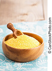 Dry raw cornmeal in wooden bowl with scoop close up...