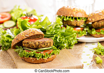 Vegan burgers with lentils and pistashios stacked on a...