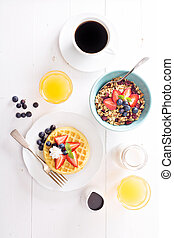Breakfast waffles with fresh berries stacked on a plate