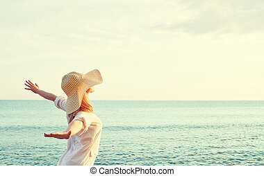 Happy woman in hat is back opened his hands, enjoys sunset -...