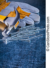 Safety glove collection of metal nails and claw hammer on...