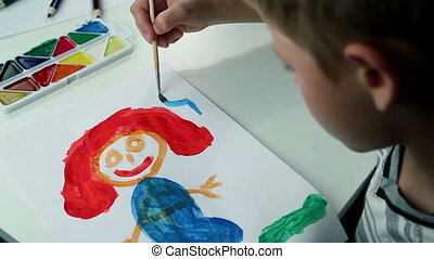 Boy Draws Paints on White Paper Mother in Blue Dress