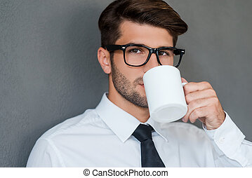 Inspired with cup of fresh coffee Confident young man in...
