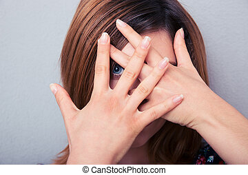 Woman looking at camera through fingers over gray background