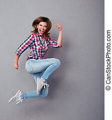 Excited woman jumping isolated on a gray - Excited young...